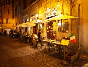 Rome, Italy - Sep 16, 2015: Tourists and local residents enjoying the night life, dining in outdoor street restaurants in the center of Rome, Italy.